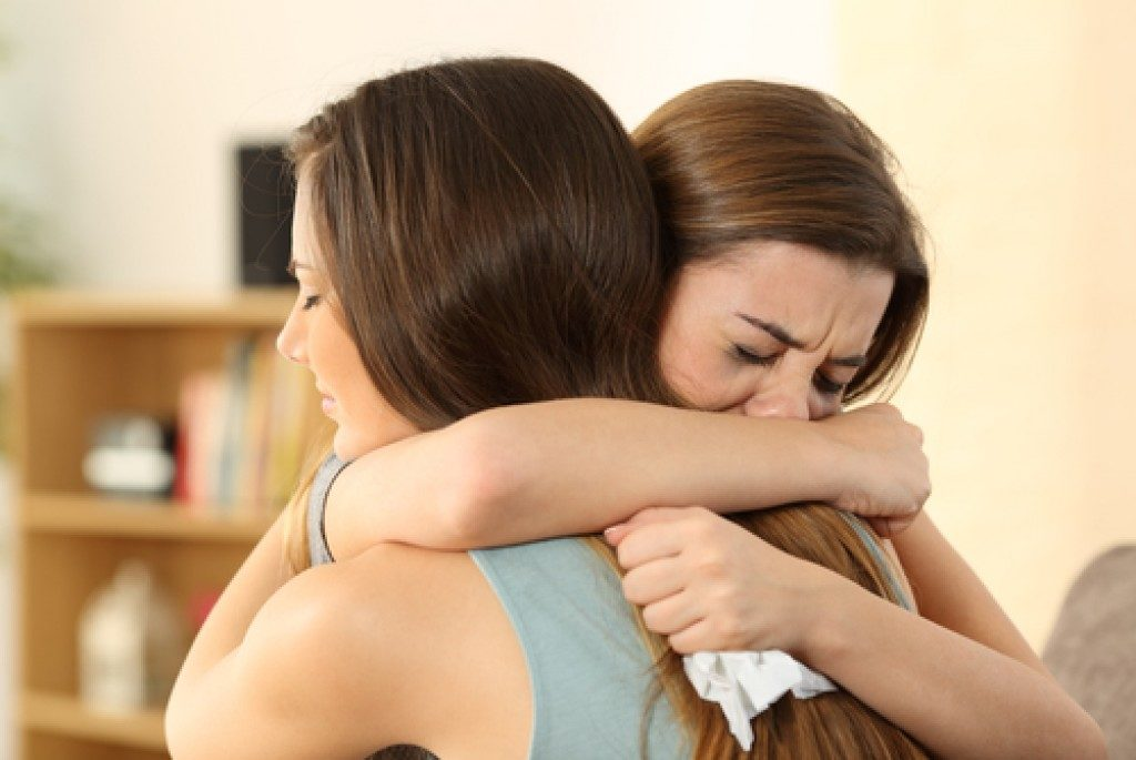 two women crying and hugging each other