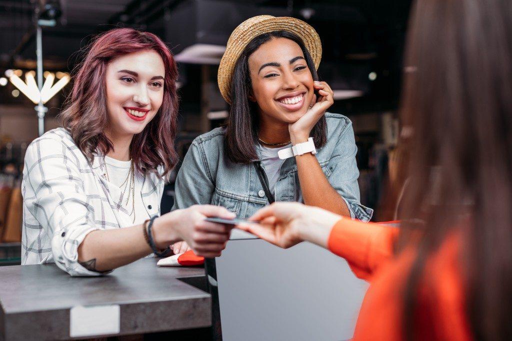 women paying using credit card