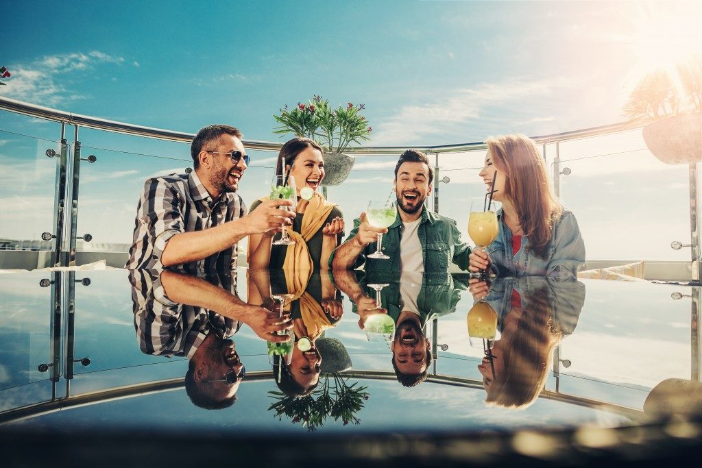 4 friends with drinks while staying outdoors