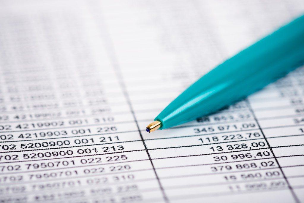blue pen on top of a balance sheet