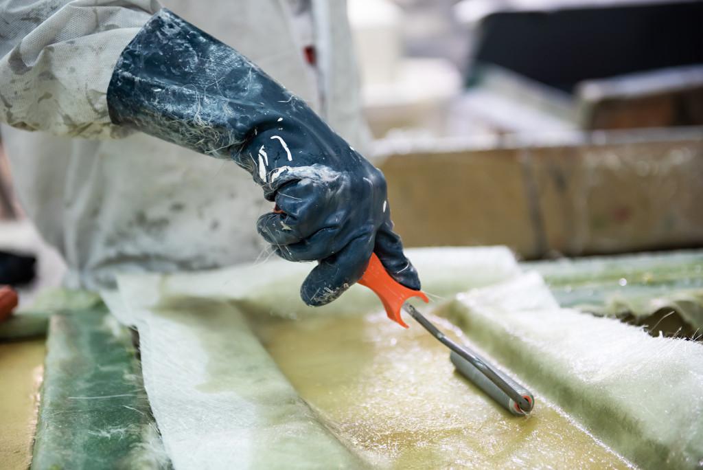 worker rolling fiberglass sheets